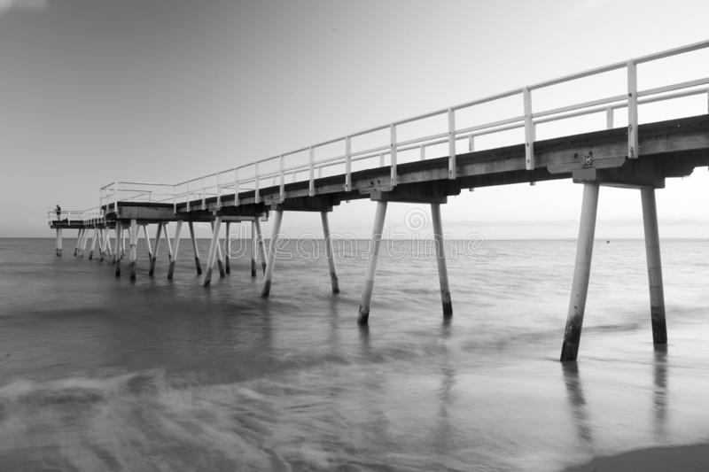 Torquay Beach Hervey Bay Australia Jetty. A long exposure shot in monochrome black and white of a beach jetty. This jetty is found at Torquay Beach in Hervey Bay stock photography