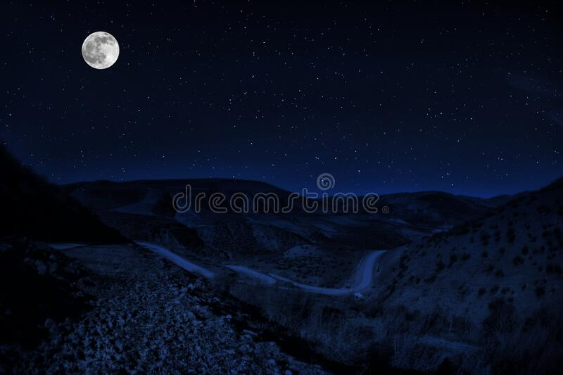 Long exposure shot. Mountain Road through the forest on a full moon night. Scenic night landscape of dark blue sky with moon. stock image
