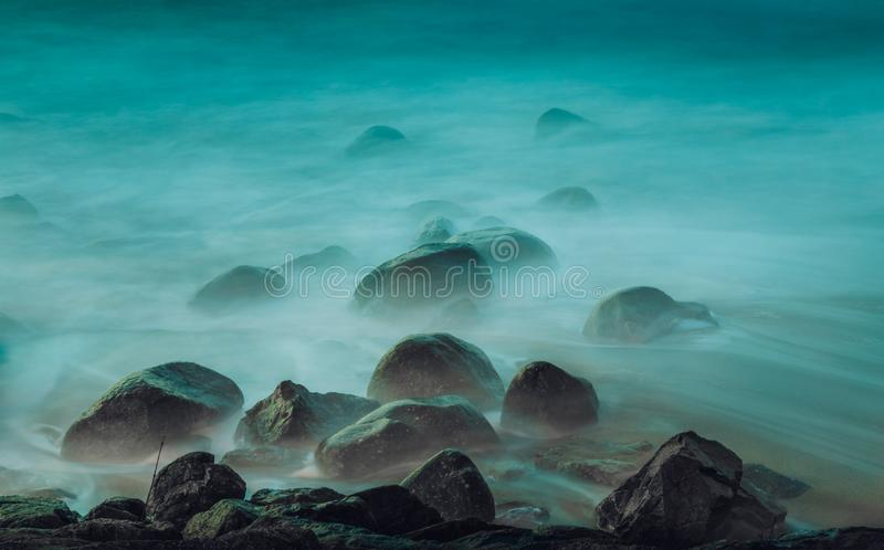 Long exposure shot of ocean waves hitting the rocks by the beach royalty free stock photography