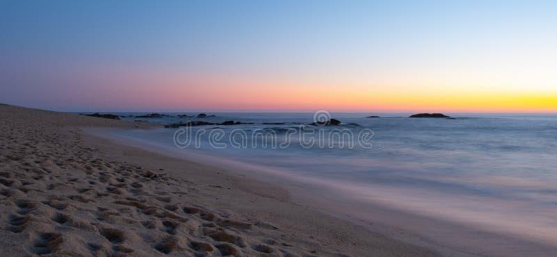 Long exposure shot over beach at dusk with milky ocean and smooth blue orange gradient sky. Dark rocks in water royalty free stock image