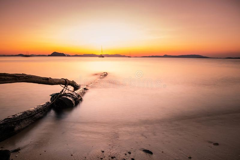 Long exposure and softness of the waves that hit the beach and beautiful timber at sunset,Koh Yao Yai,Phang Nga,Thailand. Long exposure and softness of the waves stock photo