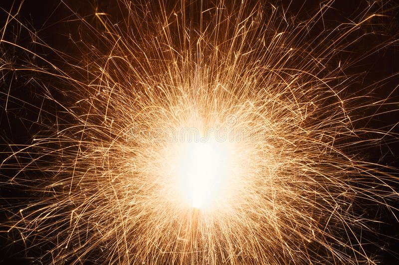 Long Exposure Of Sparkler With Flying Sparks At Night. A long exposure close-up shot of bright sparks flying from a sparkler at night royalty free stock photography