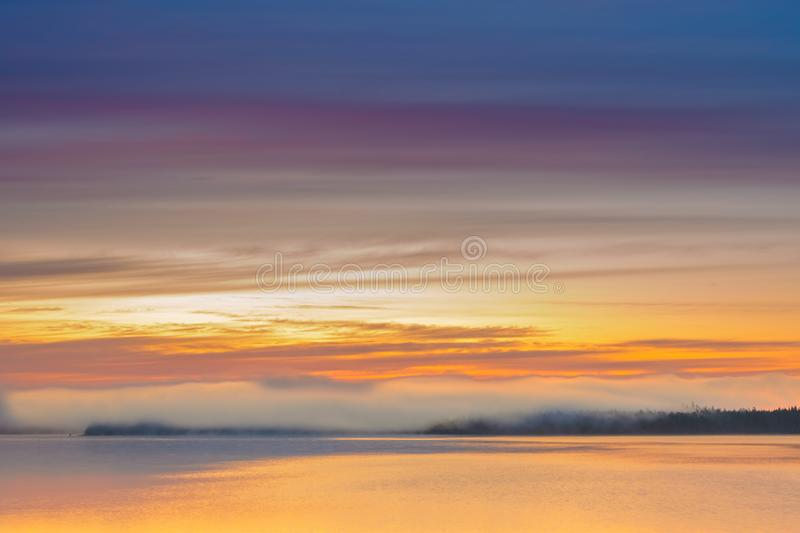 Long Exposure of Sunrise at the Paijanne lake. Beautiful scape with sunrise sky,fog, pine forest and water. Lake Paijanne, Finland.  stock photos