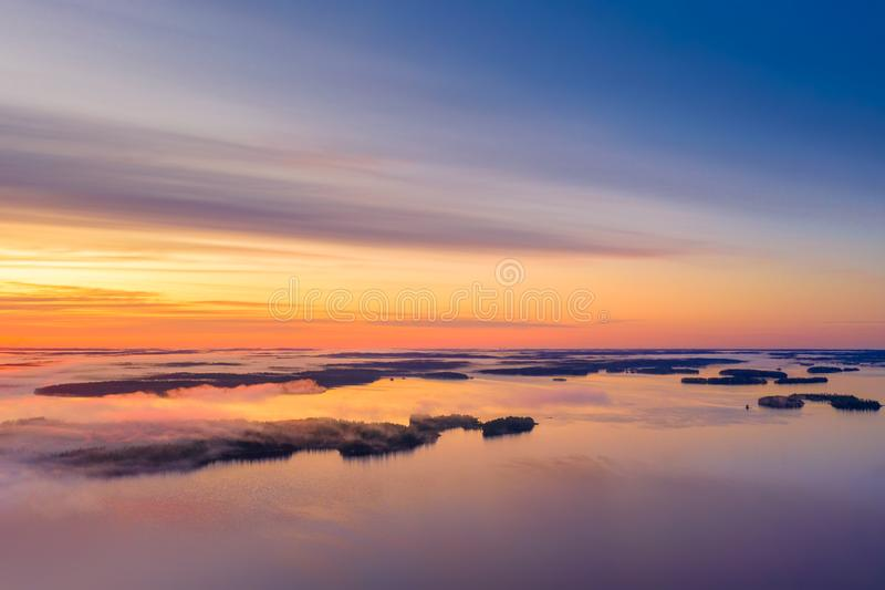 Long Exposure of Sunrise at the Paijanne lake. Beautiful scape with sunrise sky,fog, pine forest and water. Lake Paijanne, Finland.  stock photography