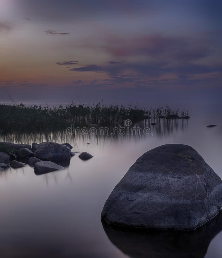 Long Exposure of Sunset at the Ladoga lake. Beautiful scape with stone beach, reeds and water. Ladoga lake, Karelia, Russia.  royalty free stock images