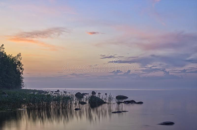 Long Exposure of Sunset at the Ladoga lake. Beautiful scape with stone beach, reeds and water. Ladoga lake, Karelia, Russia.  stock image