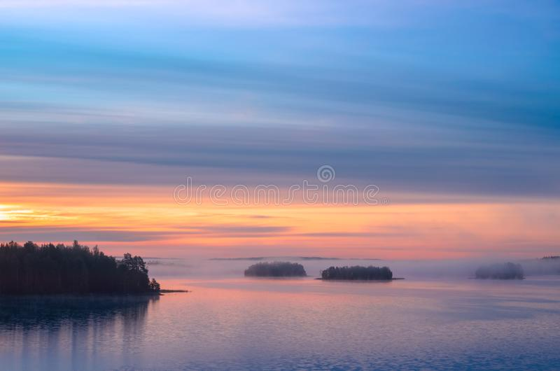 Long Exposure of Sunset at the Paijanne lake. Beautiful scape with sunrise sky, pine forest and water. Lake Paijanne, Finland.  royalty free stock image