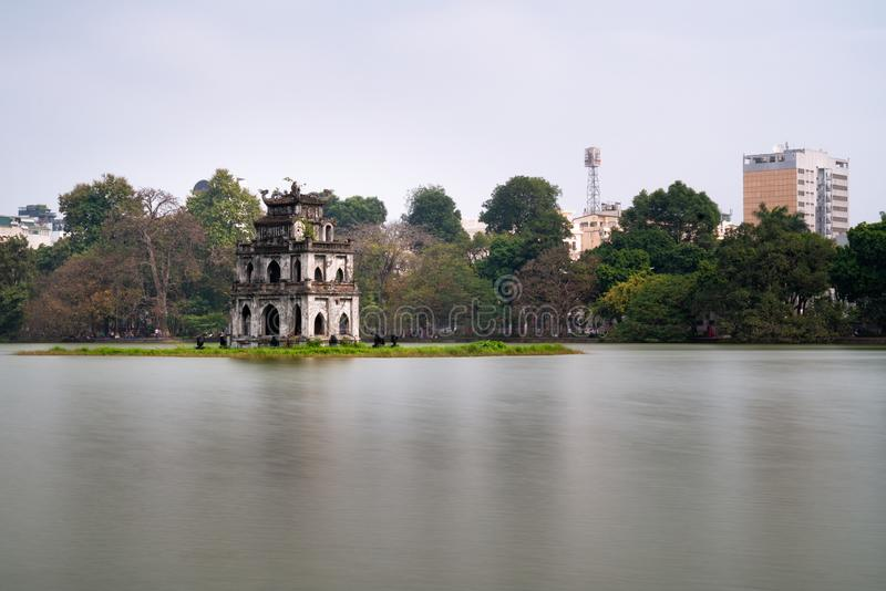 Long exposure of the turtle tower in the middle of Hoan Kiem Lake with trees and the park in the background. Hanoi, Vietnam. Long exposure of the turtle tower stock photography
