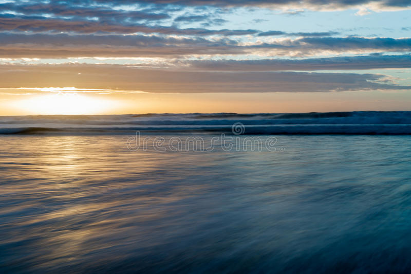 Long exposure Waitarere Beach Levin New Zealand. Waitarere Beach Levin New Zealand the distant surf and wash of sea on beach smoothed by long exposure in blue royalty free stock photography