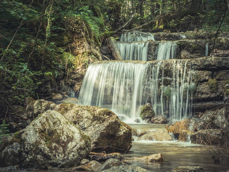 Long exposure waterfall over rocks in forest landscape royalty free stock photo