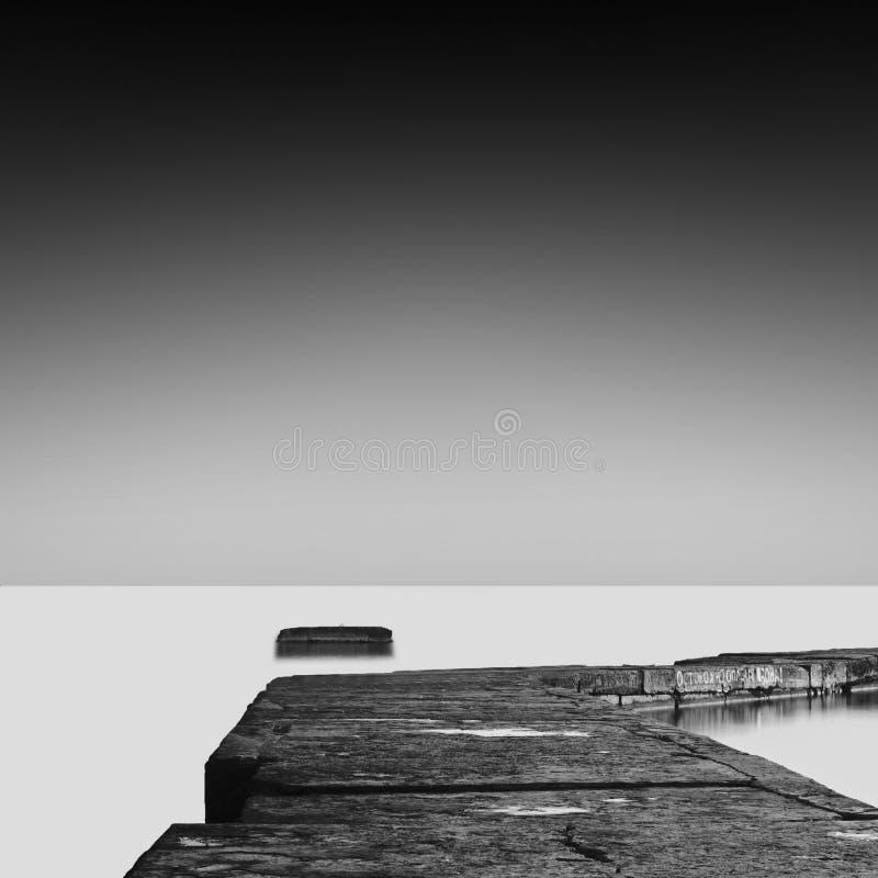 Long exposure wavecutter. Black and white minimalistic seascape / daytime long exposure / black sea, odessa, ukraine royalty free stock photo