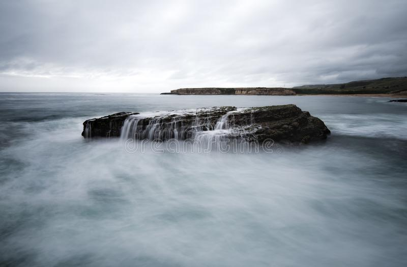 Long exposure of the waves crashing on a sea stack stock photography