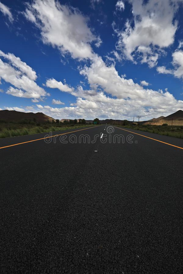 A long and flat run through a semi desert. This is an image of the N1 highway near Drie Suster in the Great Karoo. The Great Karoo is a huge semi desert in South royalty free stock image