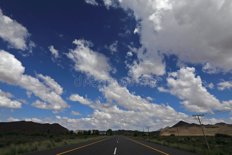 A long and flat run through a semi desert. This is an image of the N1 highway near Drie Susters in the Great Karoo. The Great Karoo is a huge semi desert in stock image