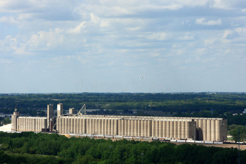 A Long Grain Elevator Surrounded By Trees. In the middle of a busy city royalty free stock photos
