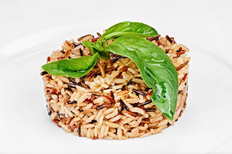 Long grain white and brown rice cooked with green leafs. Organic long grain white and brown rice cooked with green leafs isolated on white background of plate royalty free stock photo