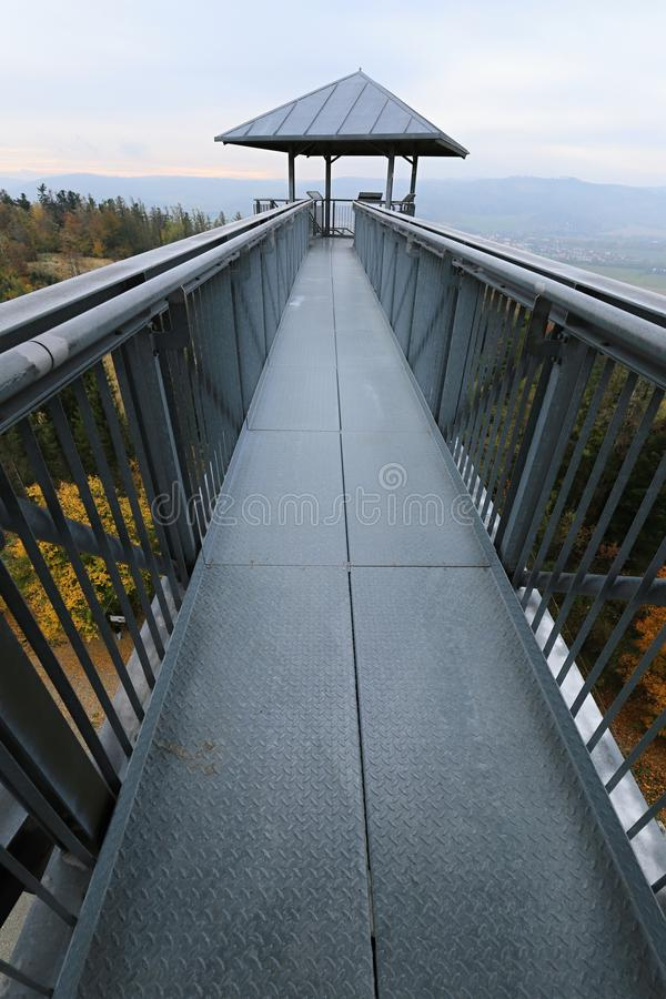 Long metal outlook tower foot bridge high above trees. Long gray metal outlook tower foot bridge high above trees stock photo