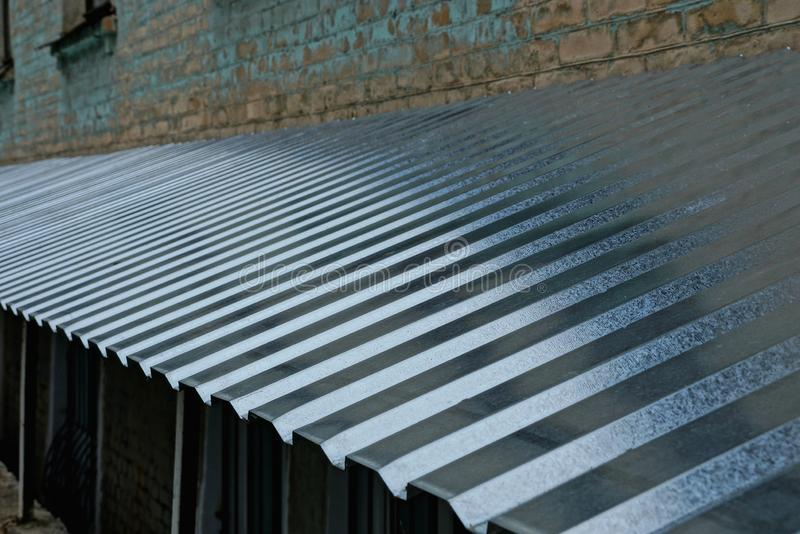 Long gray metal roof against the wall stock photos