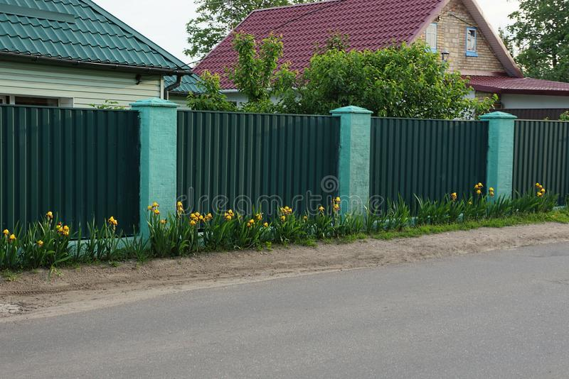 Long green metal fence in the grass and flowers stock image