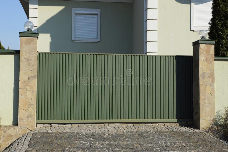 Long green metal gate in the street near the wall of the house stock photo