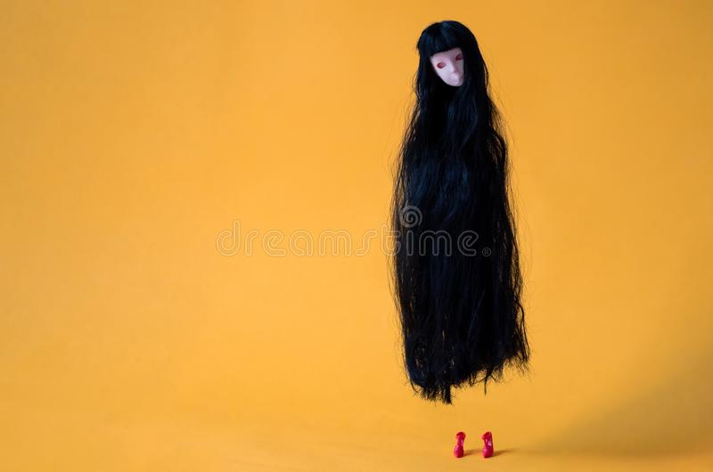 Long hair asian female ghost doll flying in the air with red high heel on the floor on orange background. Minimal Halloween scary stock image