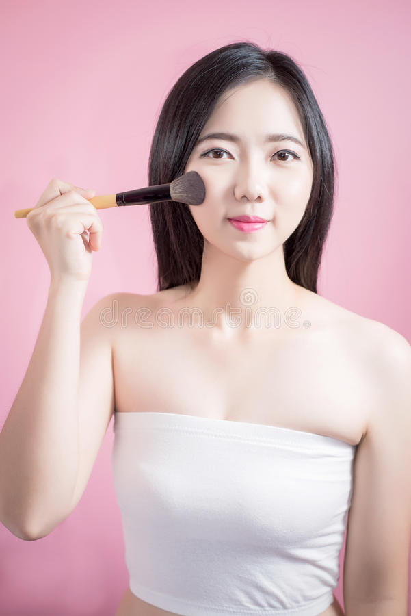 Long hair asian young beautiful woman applying cosmetic powder brush on smooth face isolated over pink background. natural makeup. stock images