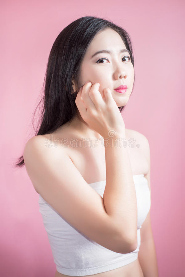 Long hair asian young beautiful woman cross arm and point finger upward isolated over pink background. natural makeup, SPA therapy royalty free stock photo