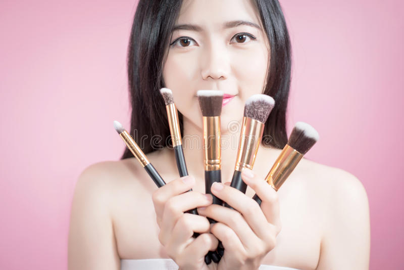 Long hair asian young beautiful woman smile and fun, touch her face and hold cosmetic powder brush set, isolated over pink. royalty free stock photos