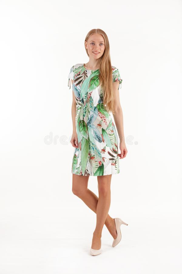 Beautiful young blonde woman in white dress with tropical print isolated on white background stock photo