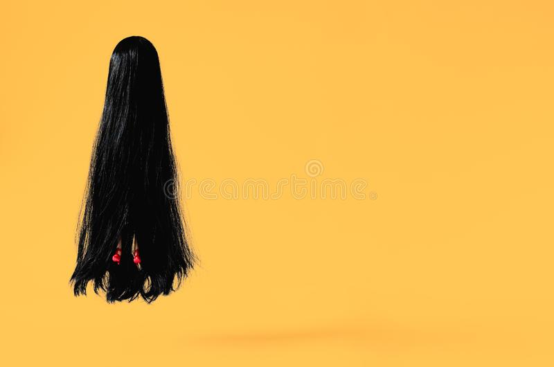 Long hair female ghost with red high heel shoe flying to the air with orange background. Minimal Halloween scary concept.  stock photo