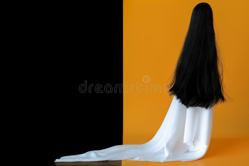 Long hair female ghost with white sheet costume with black and orange background. Minimal Halloween scary concept.  royalty free stock images