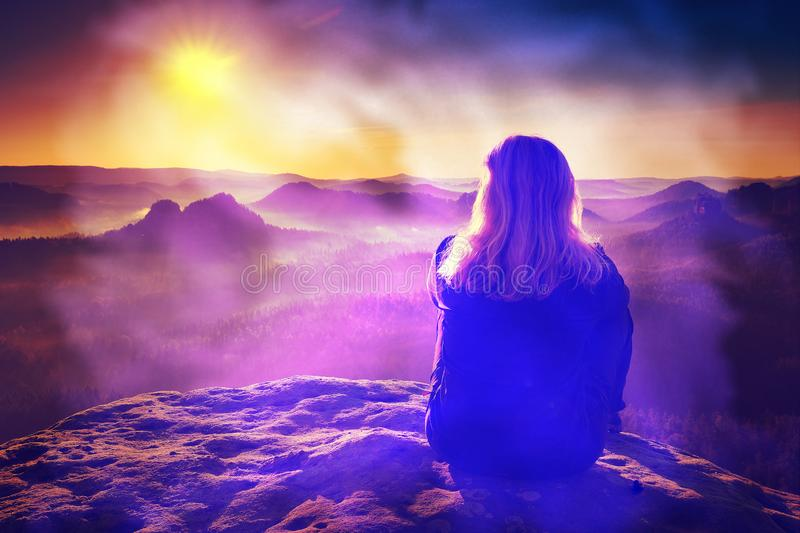Long hair female hiker relaxes above hillside watch nice sunrise. Abstract filter, wilderness, vitality, twisted, tousled, sweater, sunset, people, outdoors stock photo