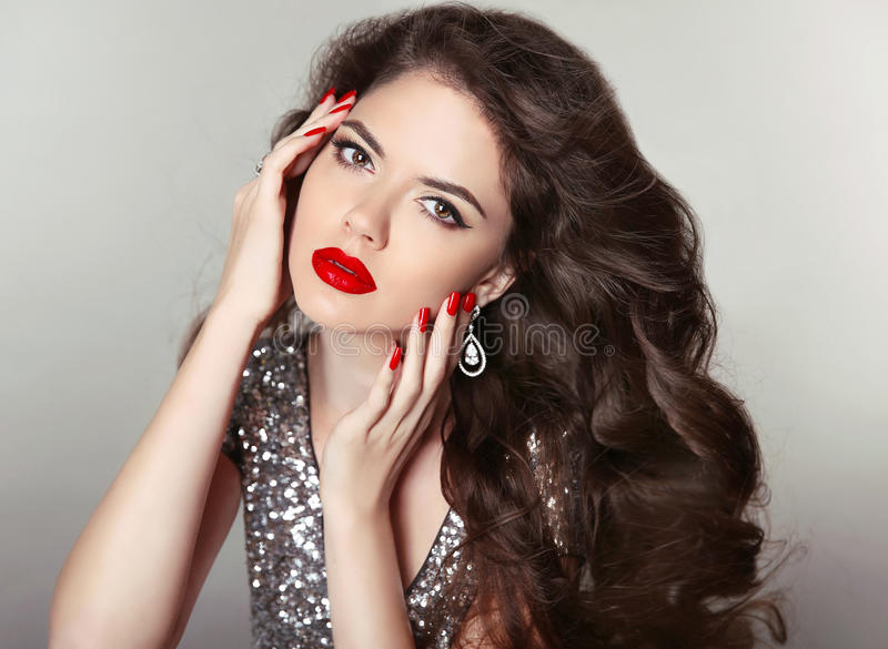 Long hair. Makeup. Beautiful girl portrait. Brunette fashion woman with red lips, manicured nails, healthy curly shiny hairstyle stock photos