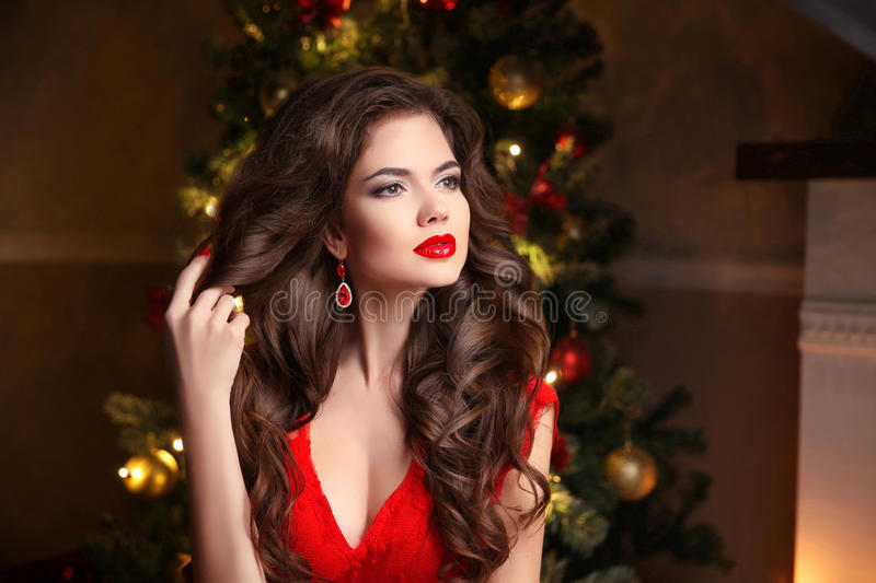 Long hair. Makeup. Christmas Woman. Beautiful girl portrait. Elegant lady in red dress with wavy healthy hairstyle over christmas royalty free stock photos