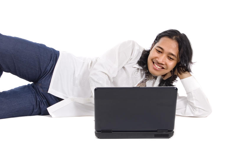 Long Hair Man and Laptop. Long hair man laying on the ground, working with laptop, isolated on white background stock photo
