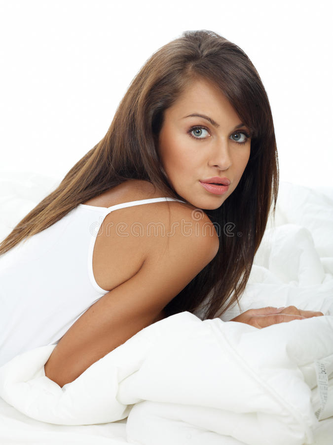Long Hair Seductive Woman Leaning on White Bed royalty free stock photo