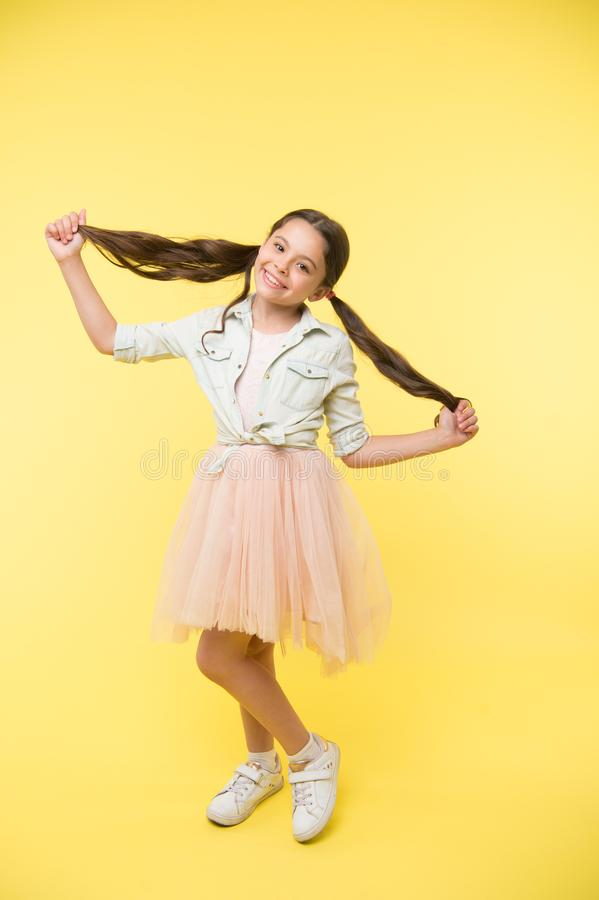 Long hair tips for kids. Kid girl charming ponytail hairstyle cute happy yellow background. Child stylish outfit holds stock image