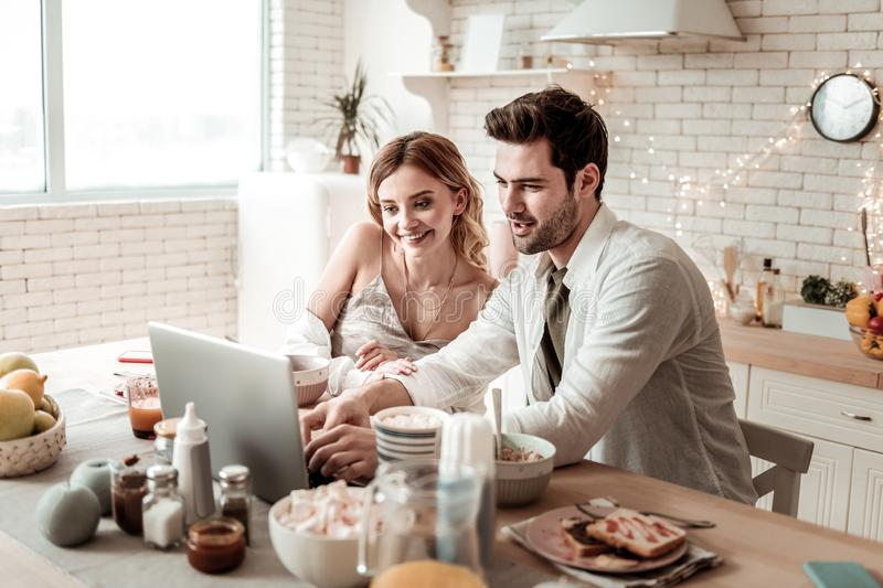 Long-haired beaming pretty woman in home clothes looking happy stock photo