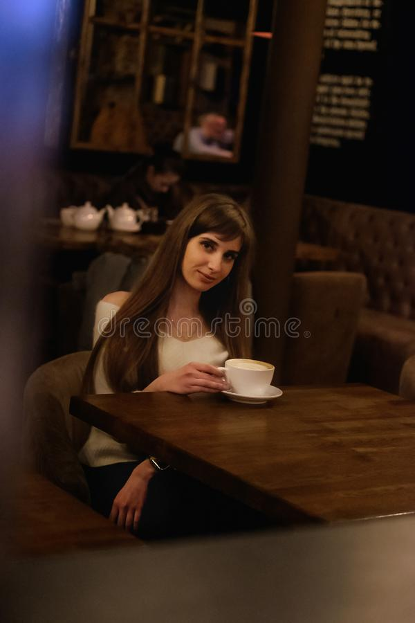 Long-haired beautiful girl in a white sweater sits in a coffee shop at a wooden table drinking coffee royalty free stock photography