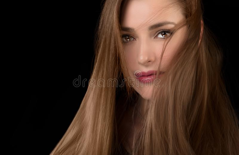 Long-haired beautiful woman with tousled hair style. Beautiful model girl with tousled hair style in a healthy long hair. Multi highlights color technique. Care stock photography