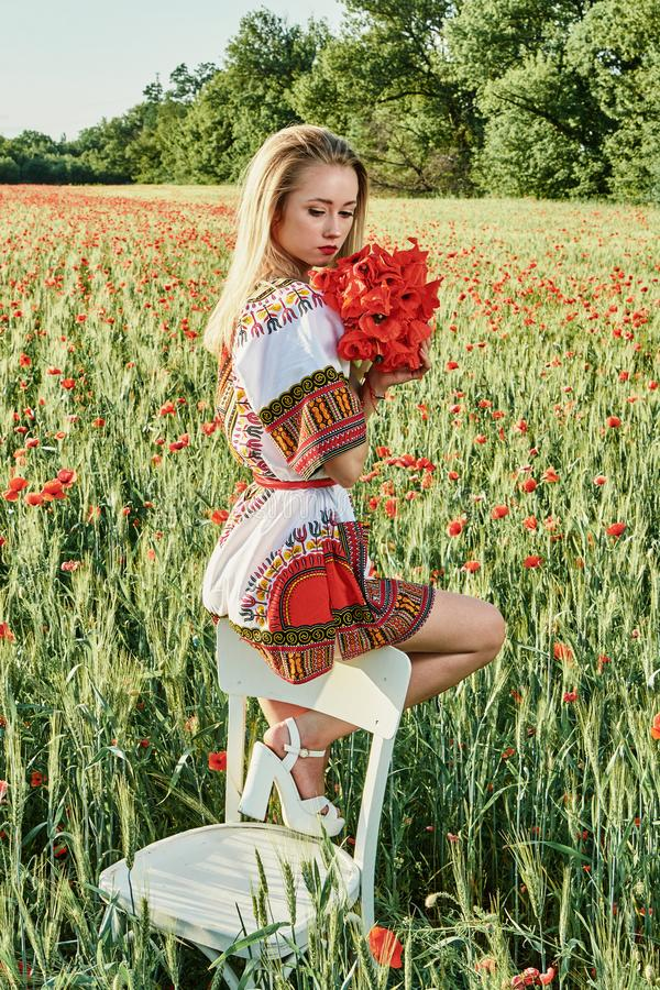 Long-haired blonde young woman in a white short dress on a field of green wheat and wild poppies stock images