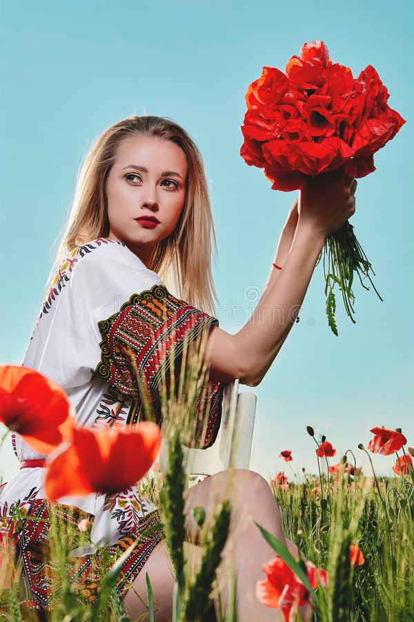 Long-haired blonde young woman in a white short dress on a field of green wheat and wild poppies royalty free stock photography