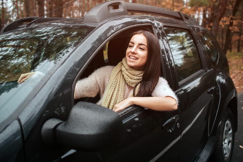 Long-haired brunette on the auto background. A female model is wearing a sweater and a scarf. Autumn concept. Autumn. Forest journey by car royalty free stock photos
