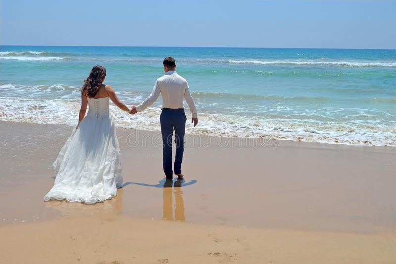 Long-haired brunette bride and groom in a suit. newlyweds holding hands, go to the sand in the water of the Indian Ocean stock images