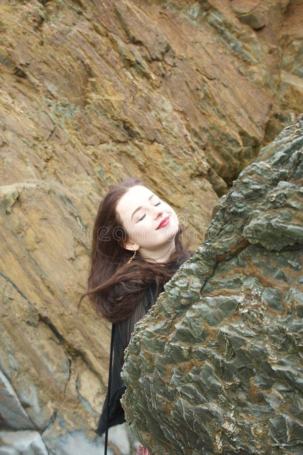 Long haired brunette girl hides behind a rock on a beach royalty free stock images