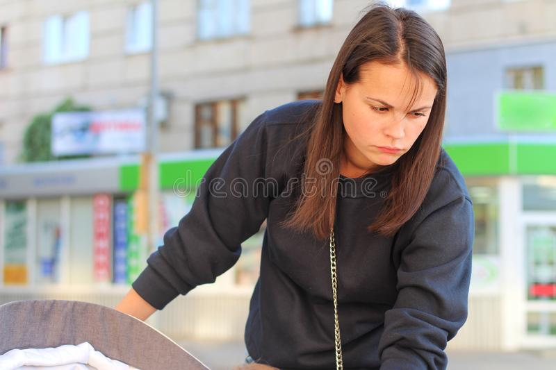 long-haired brunette girl leans over the pram on the background of shop windows. Portrait of a European woman in a blue sweatshirt royalty free stock photos