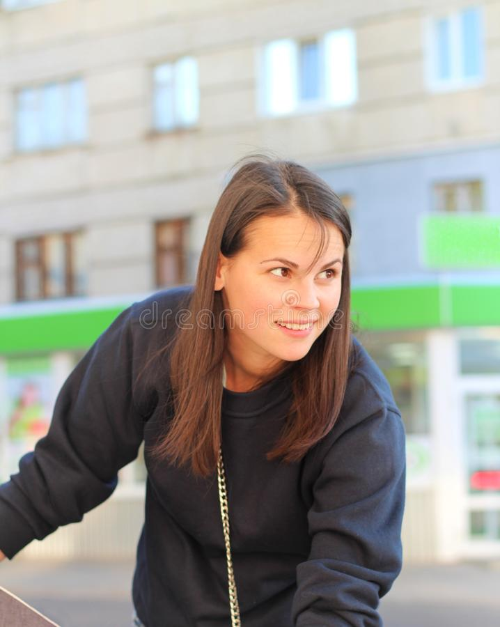 long-haired brunette girl leans over the pram on the background of shop windows. Portrait of a European woman in a blue sweatshirt royalty free stock photography