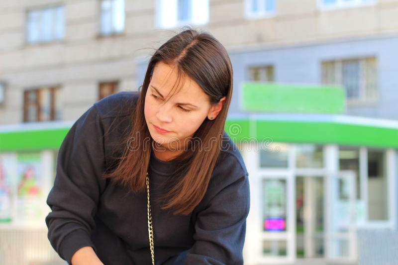 long-haired brunette girl leans over the pram on the background of shop windows. Portrait of a European woman in a blue sweatshirt royalty free stock photo
