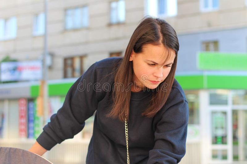 long-haired brunette girl leans over the pram on the background of shop windows. Portrait of a European woman in a blue sweatshirt stock image