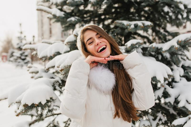 Long-haired brunette girl posing with happy face expression in winter morning. Outdoor portrait of charming european royalty free stock images